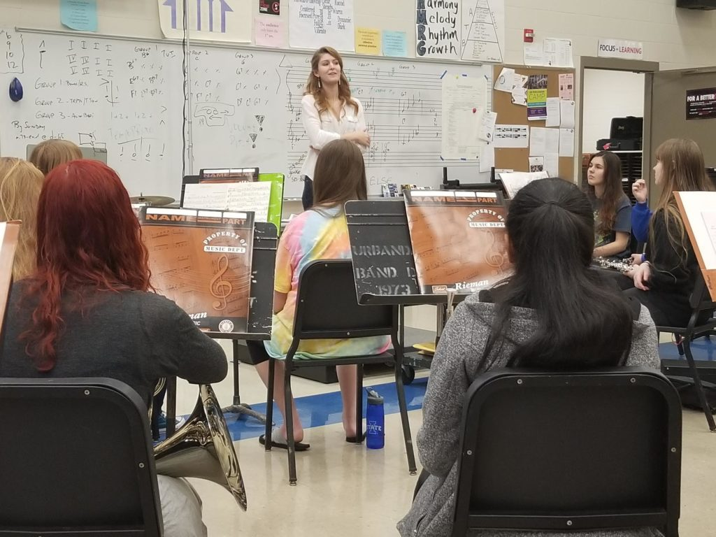 Jillian speaking with a group of young musicians
